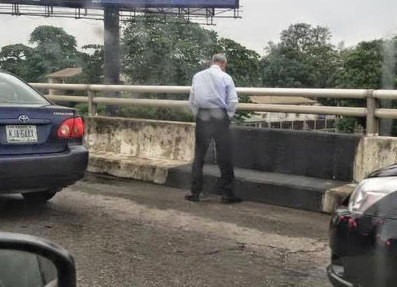 man-urinating-on-a-bridge-in-lagos