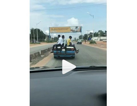 3 young boys sitting on a moving car