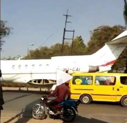 private jet being towed by tractor on a major road
