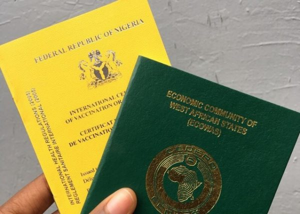 yellow fever card and Nigerian international passport held in the hand