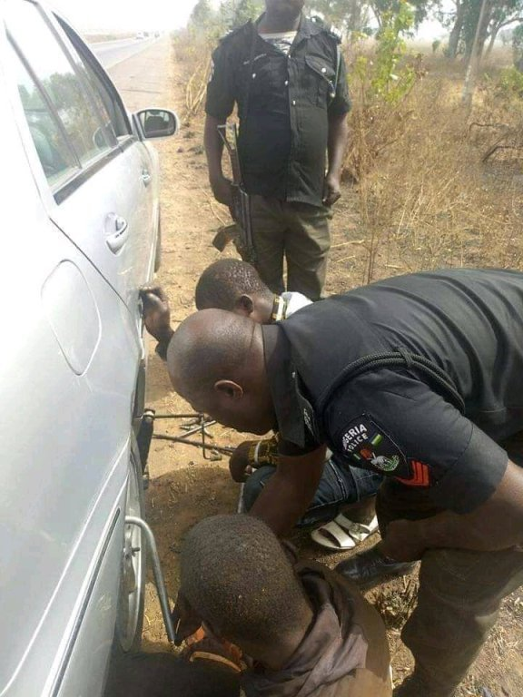 policemen help man fix car