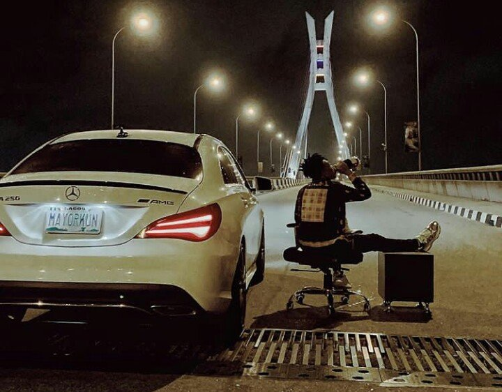 mayorkun sitting with his Benz CLA250 on Lekki-Ikoyi link bridge