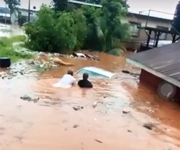 residents of Erediauwa axis of Benin-city are seen trying to pullout a submerged car from a scene of flooding.